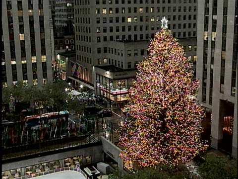 the traditional christmas tree illumines 56 rockefeller center in new york city. - albero di natale del rockefeller center video stock e b–roll