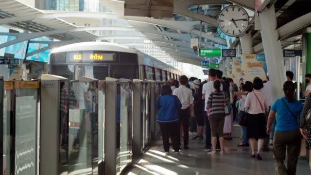 vidéos et rushes de le train arrive à la gare du ciel à bangkok. un groupe de personnes portant le masque d'attente pour le train. - patiente