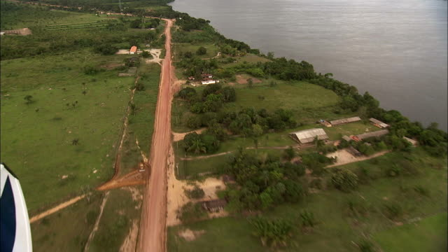 The Trans-Amazonian Highway runs through a small settlement alongside the Amazon River. Available in HD.