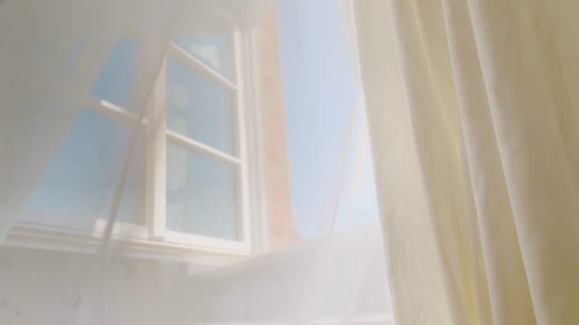 the transparent curtain blows in the summer wind at the open window - window stock videos & royalty-free footage