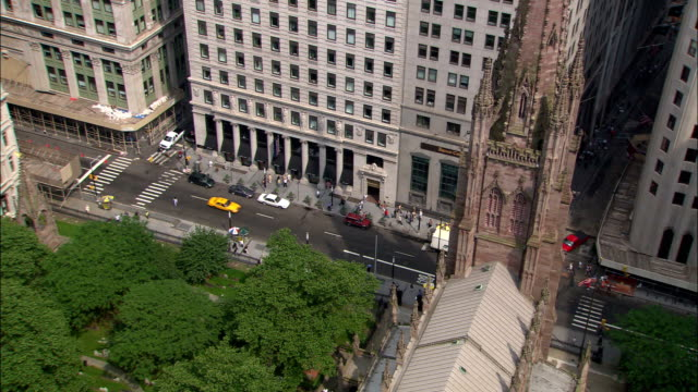 the trinity church steeple  towers over a park and a new york city street. - steeple stock videos & royalty-free footage