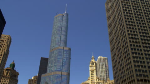 the trump international hotel, tower and wrigley building tower over the chicago river in downtown chicago, illinois. - wrigley building video stock e b–roll