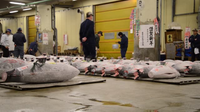 The Tsukiji Market stands in Tokyo Japan on Thursday Jan 5 Pedestrians walk past road signs displayed outside the Tsukiji Market Buyers inspect...