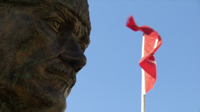 The Turkish flag flies from a flagpole near a state of Mustafa Kemal Ataturk in Istanbul.