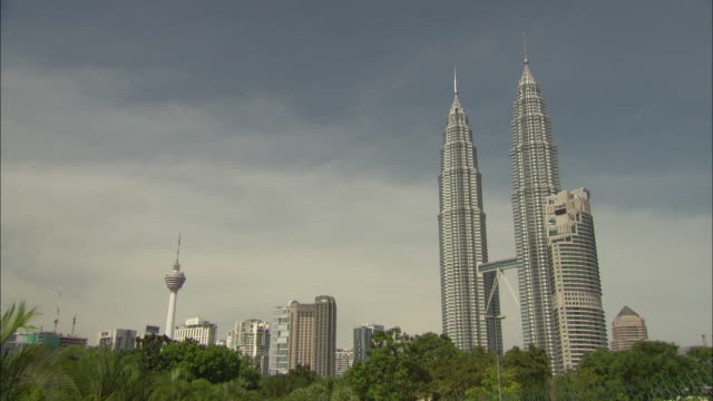 the twin petronas towers loom over kuala lumpur. - petronas twin towers stock-videos und b-roll-filmmaterial