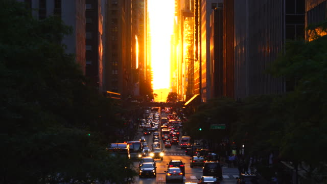 the two days later the manhattan henge. the setting sun is aligned with the 42nd streets and illuminates the traffic and buildings on the grid of manhattan, new york city on jun. 01 2017. the sun is passing among 42nd street skyscrapers. - manhattan stock-videos und b-roll-filmmaterial