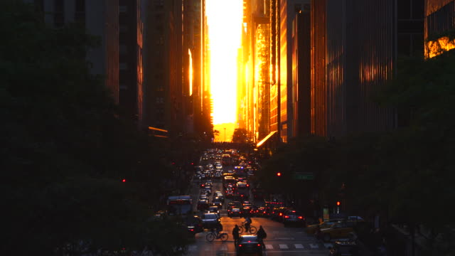 The two days later the Manhattan Henge. The setting sun is aligned with the 42nd streets and illuminates the traffic and buildings on the grid of Manhattan, New York City on Jun. 01 2017. The sun is passing among 42nd street skyscrapers.