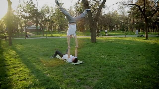 stockvideo's en b-roll-footage met de twee gymnastische acrobatische mannen over het geheel genomen vormen - acrobaat
