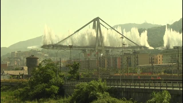 the two remaining towers of the motorway bridge in the italian city genoa that collapsed nearly a year ago killing 43 people were demolished on... - demolito video stock e b–roll