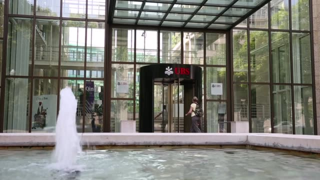 the ubs ag logo sits on display outside a branch of the bank in basel switzerland on tuesday july 23 visitors pass a fountain outside the offices of... - hauptfirmensitz stock-videos und b-roll-filmmaterial