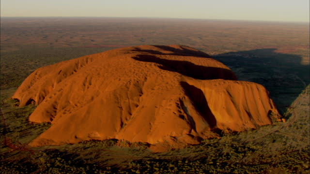 the uluru sandstone rock formation changes color gradually. - エアーズロック点の映像素材/bロール