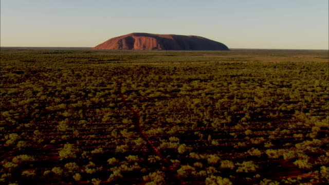 the uluru sandstone rock formation lies beyond a vast grassland. - エアーズロック点の映像素材/bロール