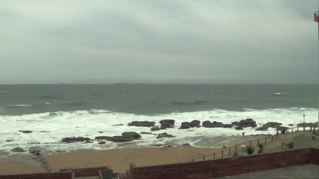 The Umhlanga Rocks Lighthouse overlooks a rocky shore. Available in HD.
