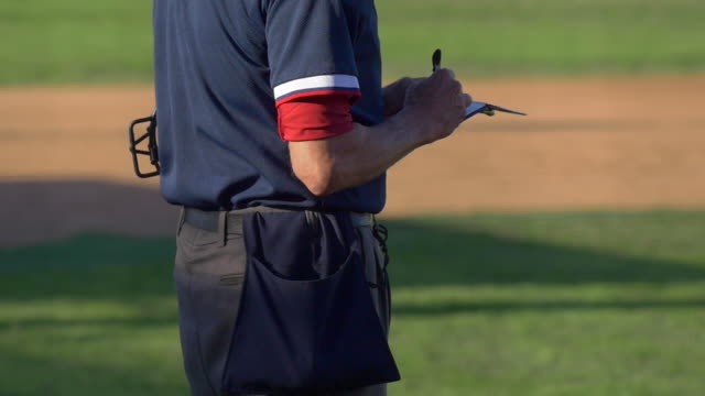 the umpire at a baseball game with his score notepad. - slow motion - notizbuch stock-videos und b-roll-filmmaterial
