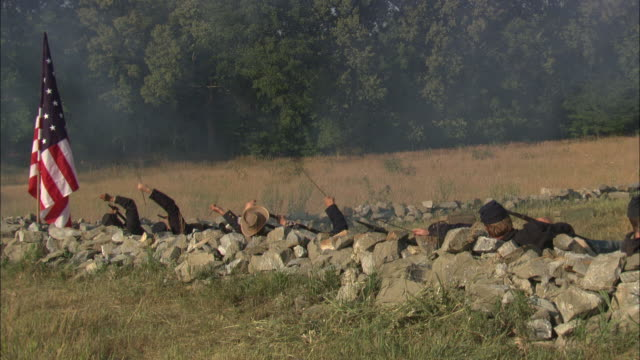 the union flag waves near a rock wall where union soldiers fire rifles during  a civil war battle. - reenactment stock videos and b-roll footage