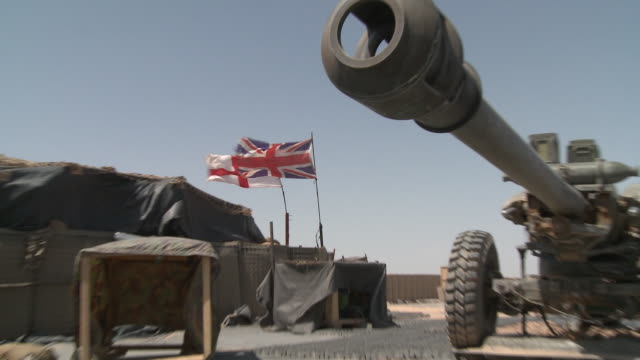 vídeos de stock e filmes b-roll de the union jack and saint george's flag wave in front of a tent near a british artillery piece. - helmand