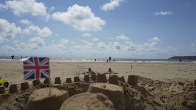 The Union Jack Flag on top of a Sand Castle at the sea side.