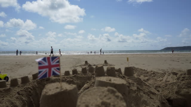 the union jack flag on top of a sand castle at the sea side. - patriotism stock videos and b-roll footage