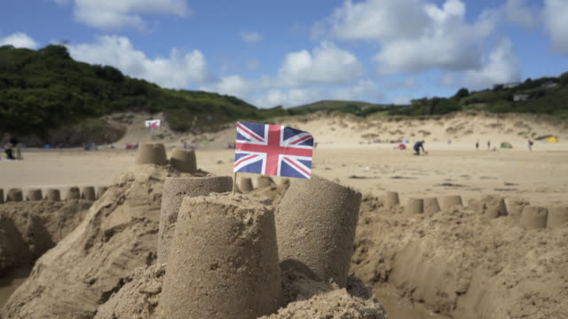 the union jack flag on top of a sand castle at the sea side. - union jack stock videos & royalty-free footage
