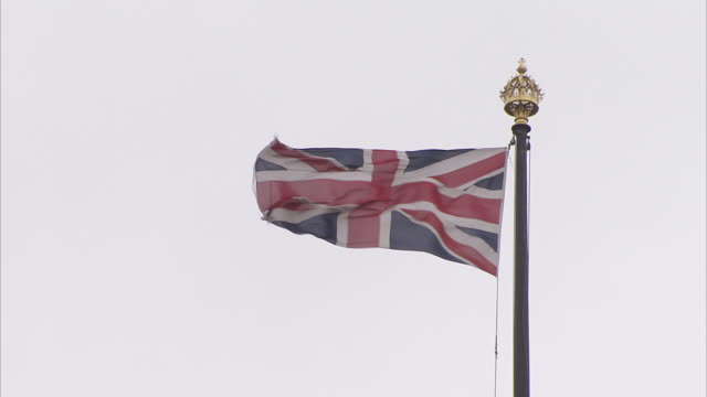 the union jack flies above the houses of parliament in london england. available in hd. - 旗棒点の映像素材/bロール