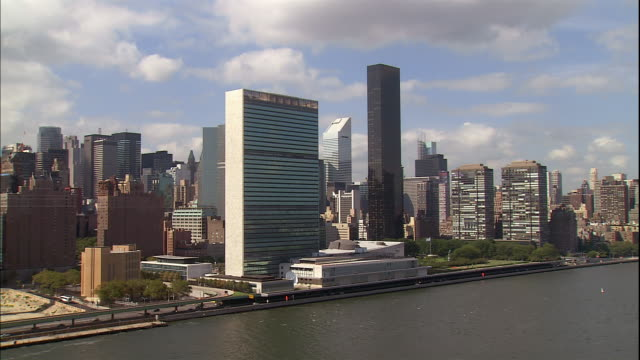 the united nations building towers in midtown manhattan. - united nations building stock videos and b-roll footage