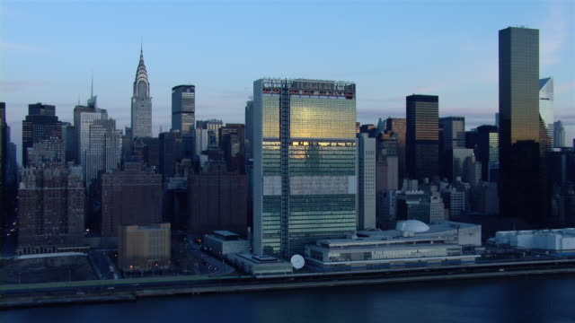 the united nations headquarters at sunrise in midtown manhattan, new york city. - united nations building stock videos and b-roll footage