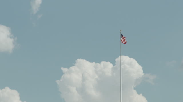 the united states flag flies from a tall flagpole in washington, d.c., usa. - stars and stripes stock videos & royalty-free footage