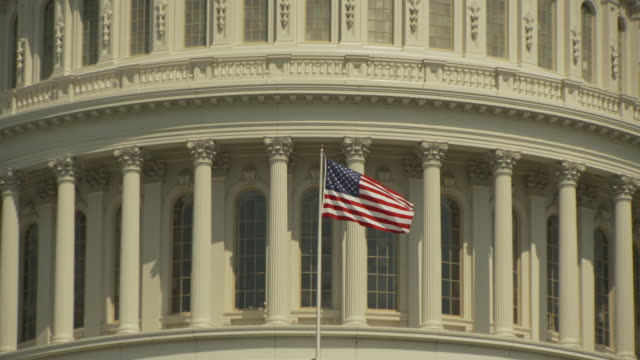 The United States national flag flies from a flagpole on the Capitol Building in Washington, D.C., USA.