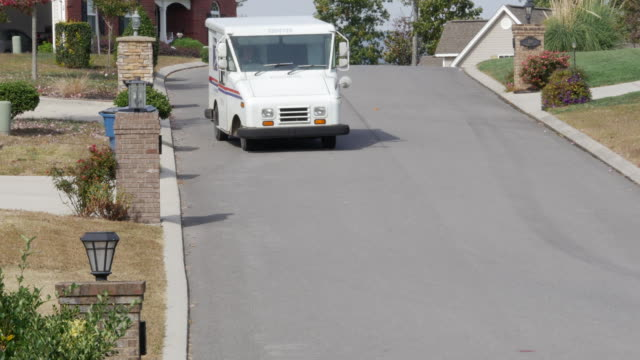 the united states postal service truck is delivering mails in the subdivision in usa. - letterbox点の映像素材/bロール
