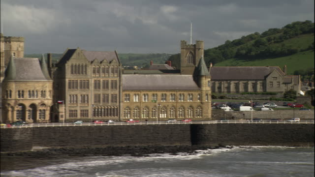 vídeos de stock, filmes e b-roll de the university of wales and castle ruins fill the coastline of aberystwyth. - aberystwyth