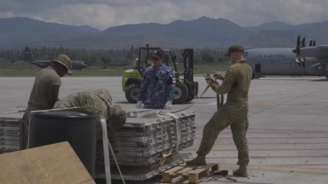 vídeos de stock, filmes e b-roll de the u.s. air force deployed c-130 hercules and military personnel to deliver and unload humanitarian aid to indonesia in support of usaid's efforts... - planejamento de emergências