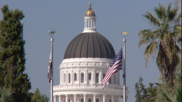 The U.S. and California state flags fly in front of the California State Capitol.