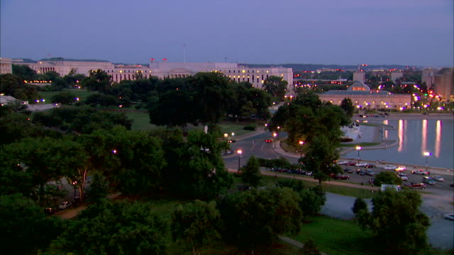 The U.S. Capitol Building faces leafy trees and the Potomac River in Washington, D.C.