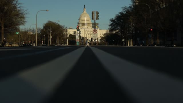 vídeos y material grabado en eventos de stock de the u.s. capitol sits in the background as light traffic goes by on pennsylvania avenue during the coronavirus pandemic on april 2, 2020 in... - virginia estado de los eeuu