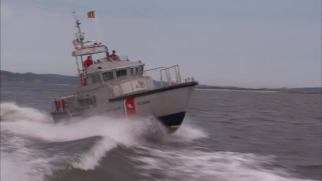 the u.s. coast guard speeds across the wake of another boat. - coast guard stock videos & royalty-free footage