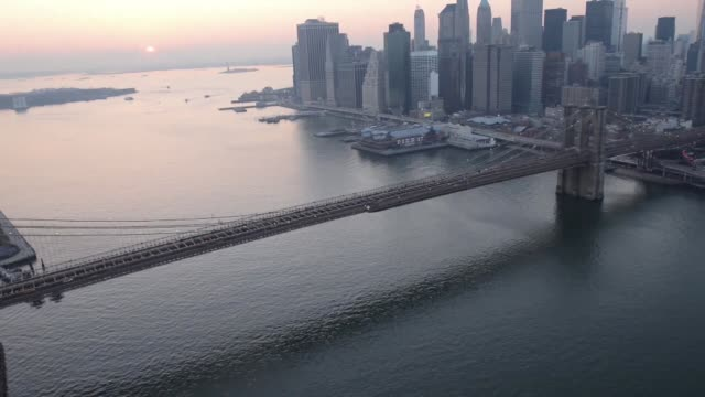 the u.s. flag flies as cars drive over the brooklyn bridge to downtown manhattan in this aerial photograph taken with a tilt-shift lens in new york,... - brooklyn bridge stock videos & royalty-free footage