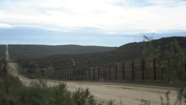 stockvideo's en b-roll-footage met ws pan the usa and mexican border wall along san diego, california and tijuana, mexico - grens
