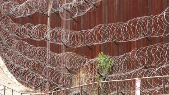 vidéos et rushes de the us/mexico border fence in nogales, arizona usa - fil de fer
