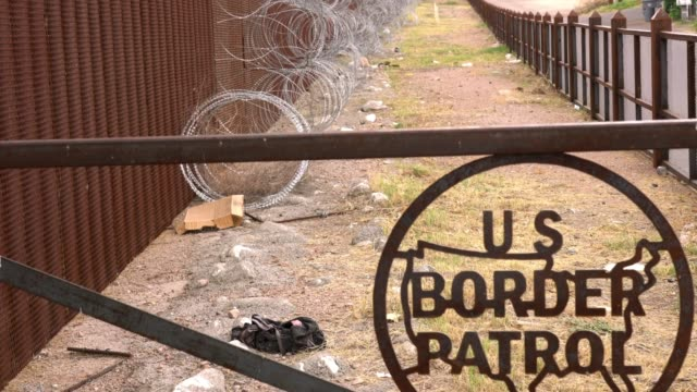 the us/mexico border wall with us border patrol sign in nogales, arizona usa - international border barrier stock videos & royalty-free footage