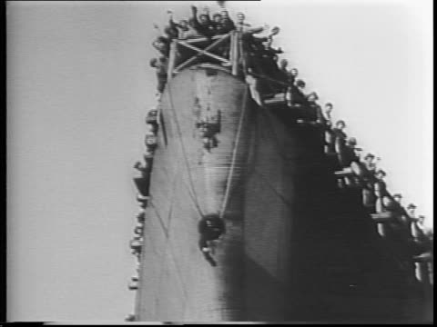 The USS Normandie gets ready to sail for the first time since August 1939 / wide shot of harbor and docks / men on bow wave / workmen waving / aerial...