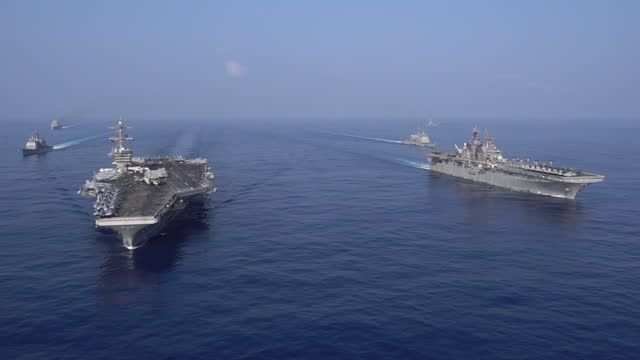 the uss theodore roosevelt carrier strike group transits in formation with the makin island amphibious ready group in the south china sea april 9,... - 米国海軍点の映像素材/bロール