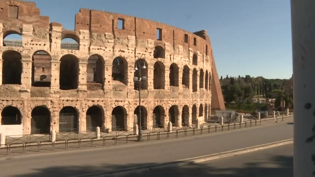the usually very touristic area surrounding rome's colosseum is empty as the italian government signed off on strict quarantine measures to fight the... - colosseo video stock e b–roll