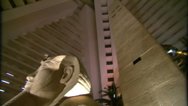 the vaulted ceiling of the luxor hotel in las vegas towers over a sphinx sculpture. - las vegas stock videos & royalty-free footage