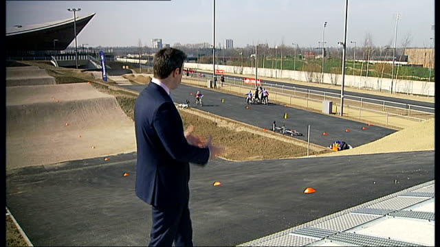 the velopark reopens for public use anonymous shots children on bikes on undulating track reporter to camera cyclists away on bumpy bmx track - holprig stock-videos und b-roll-filmmaterial