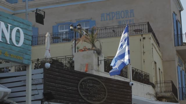 the venetian era harbour and greek flag at the mediterranean port of chania, crete, greek islands, greece, europe - greek flag stock videos & royalty-free footage