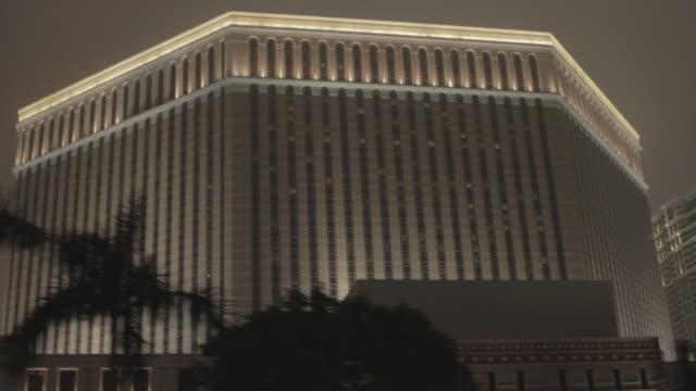 the venetian macao resorthotel palm trees street lights fg cloudy dark sky bg - cotai strip stock videos and b-roll footage