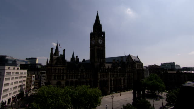 the victorian clock tower of the manchester city hall dominates the manchester skyline. available in hd. - rathaus stock-videos und b-roll-filmmaterial