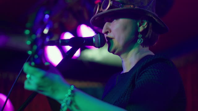 the video portrait of the mature, 45-years-old, woman, musician and singer, wearing the steampunk costume with the hat and googles - live event stock videos & royalty-free footage