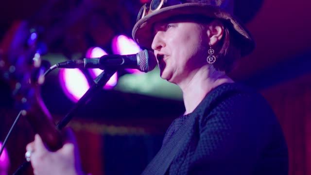 vídeos de stock, filmes e b-roll de o retrato vídeo de maduro, 45 anos de idade, mulher, músico e cantor, vestindo o traje steampunk com o chapéu e os googles - violão