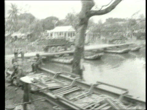 battle of hue showing landing craft on the huong river and firing from craft / us troops advance / fighting in the city including soldier with copy... - ベトコン点の映像素材/bロール